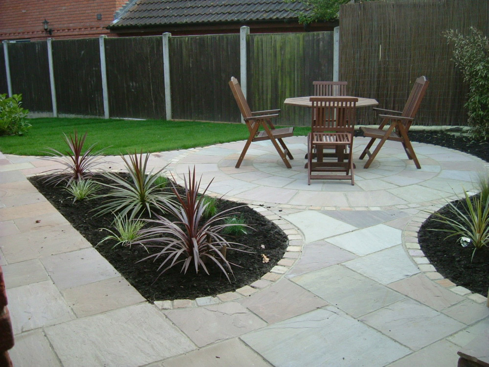 Beige riven sandstone setts 100x100mm with paving and circle. Private garden' designed and built by John Charles Landscapes.