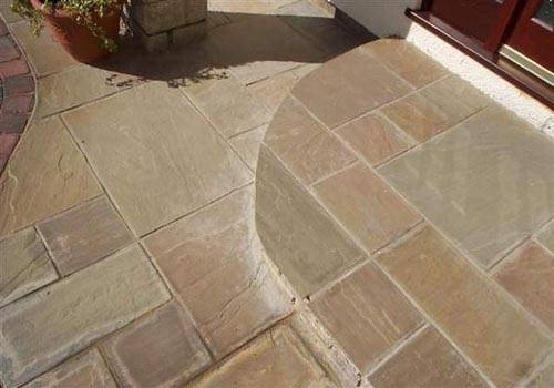 Beige Riven Sandstone Paving laid in a mix of sizes in Private Garden.