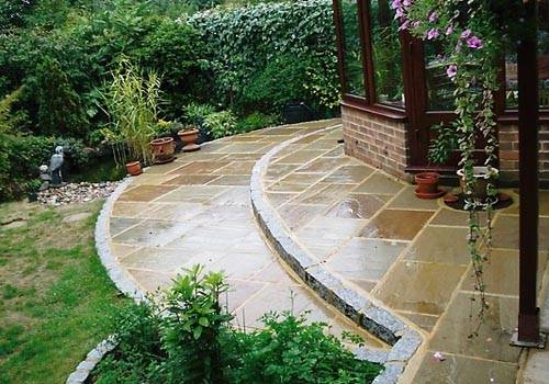 Beige Riven Sandstone Paving (pictured here when wet). Laid with Silver Grey Granite Setts in Private Garden