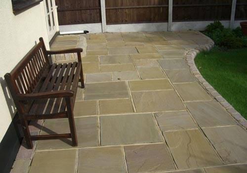 Beige Riven Sandstone Paving laid in a mix of sizes to create a Patio Area in a Private Garden.