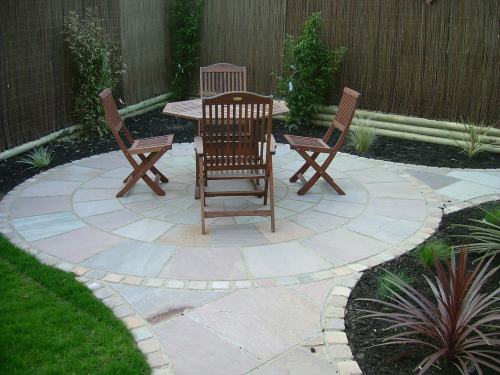 Beige sandstone circle with 100x100mm setts and paving. Private garden designed and built by John Charles Landscapes.