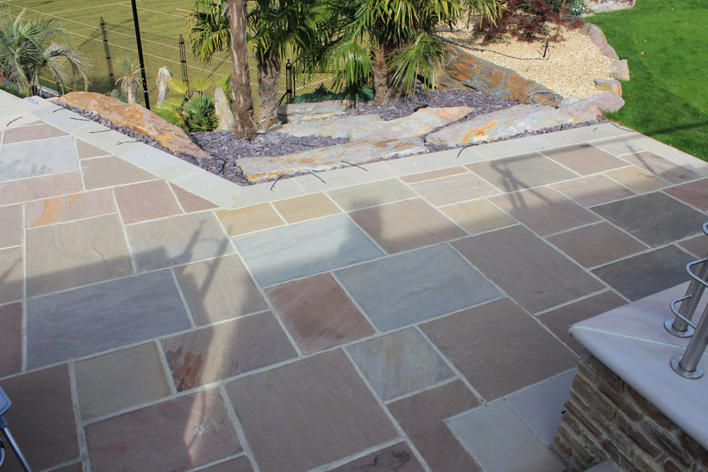 Beige riven sandstone paving' private patio area. Also pictured is plum slate shale and purple standing stones. Garden designed and built by J. Wenman & Sons. For further images of this job please visit our Projects-Private Places Gallery.