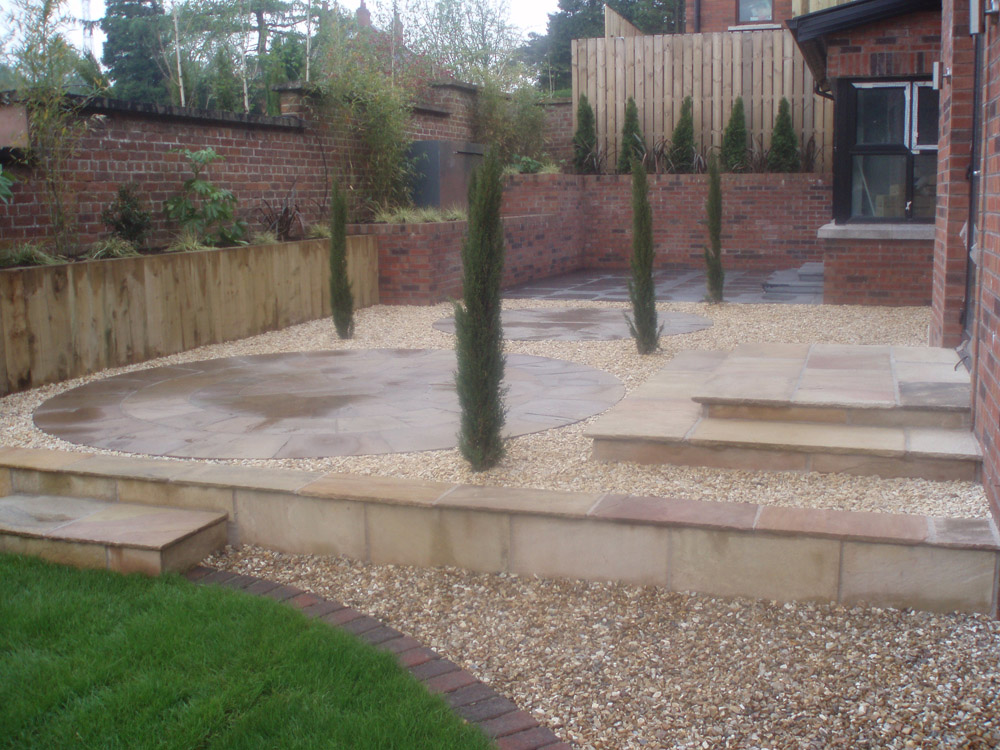 Beige riven sandstone paving with matching circles and buff flint gravel. Private garden' Ireland' by Maurice Maxwell Garden Designs.