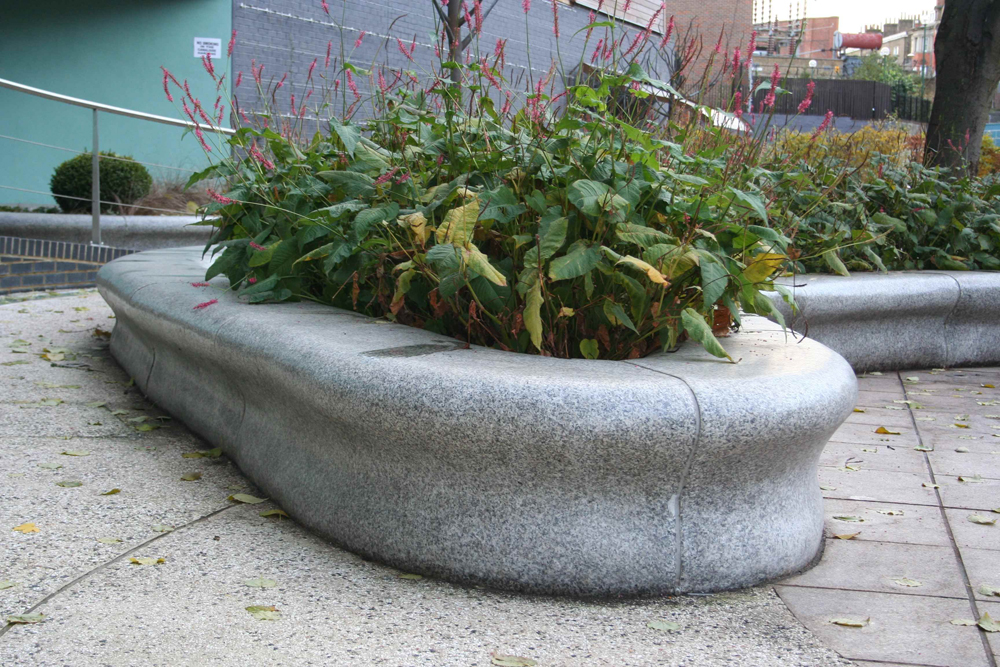 The highlight of this exciting scheme on the banks of the Grand Regent Canal are the shapely granite planter seats. Produced in silver grey granite with a honed finish they weave their intricate pattern across the contrasting pink coloured granite paving – Hand made in China the silver grey honed planter seats were produced to an exacting specification and a very tight tolerance. The individual segments of the planters were fitted together and numbered at the factory prior to shipping to ensure a smooth fit when fixed on site. An imaginative and brave design has proved very practical and remarkably good value as well as being great on the eye.