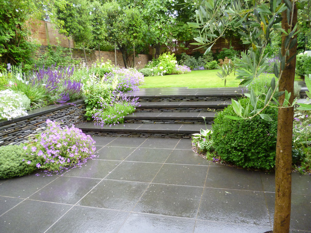 Black basalt paving and black paddlestone walling (pictured here when wet). Private garden designed by Julie Toll Landscape & Garden Design and built by The Garden Company Ltd.