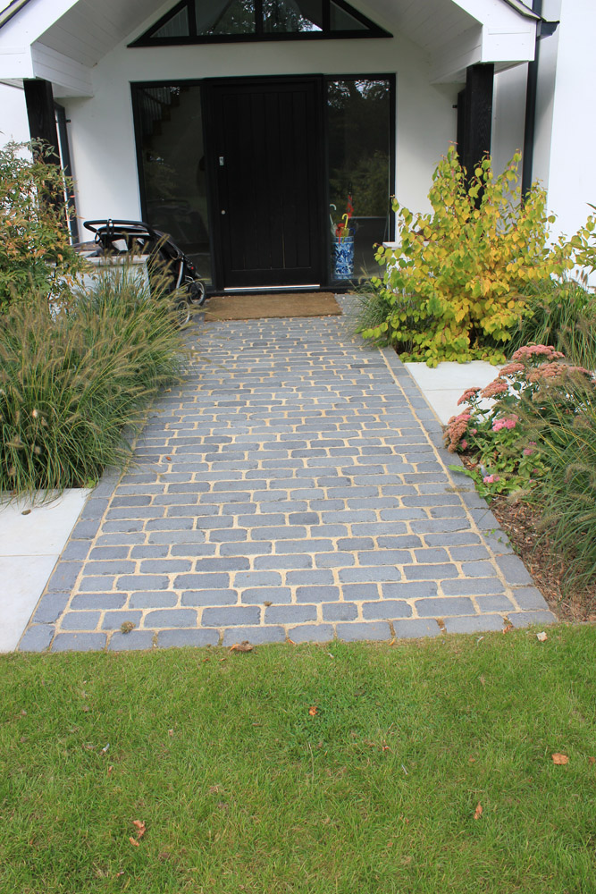 Black basalt temple setts and grey sawn & sandblasted sandstone paving. Entrance to private property' designed and built by New Eden Landscapes. For further images of this job please visit our Projects-Private Places Gallery.