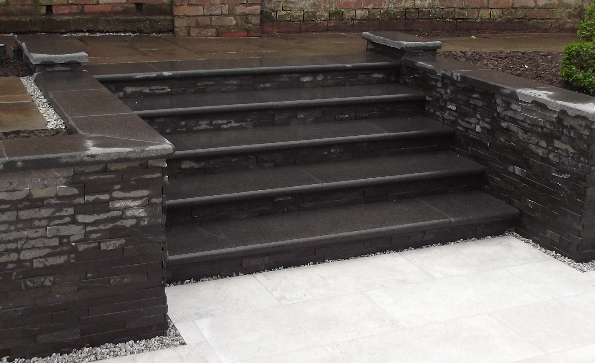 Private garden by Jeff Annannd featuring our Black Basalt Steps and Coping, Charcoal Tier and our Mijo Porcelain Paving in Amabile.