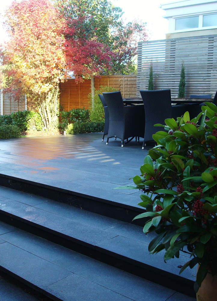 Blue grey granite plank paving' pictured here when wet. Private garden designed and built by the homeowne