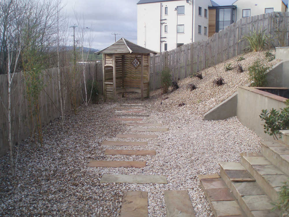 Buff flint gravel 10mm with golden flint gravel and green riven sandstone paving. Private garden in Ireland designed and built by Maurice Maxwell Garden Designs.