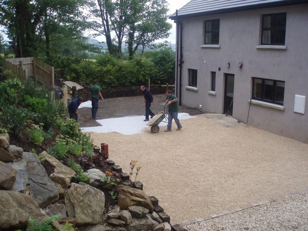 Buff Flint 10mm being laid to fill Cedagravel®' gravel stabilisation' in a private garden' Ireland. Designed and built by Maurice Maxwell Garden Designs.