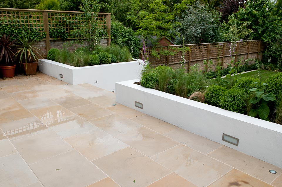Buff sandstone paving (pictured here when wet). Private garden designed and built by Belderbos Landscapes. For further images of this job please visit our Projects Gallery.