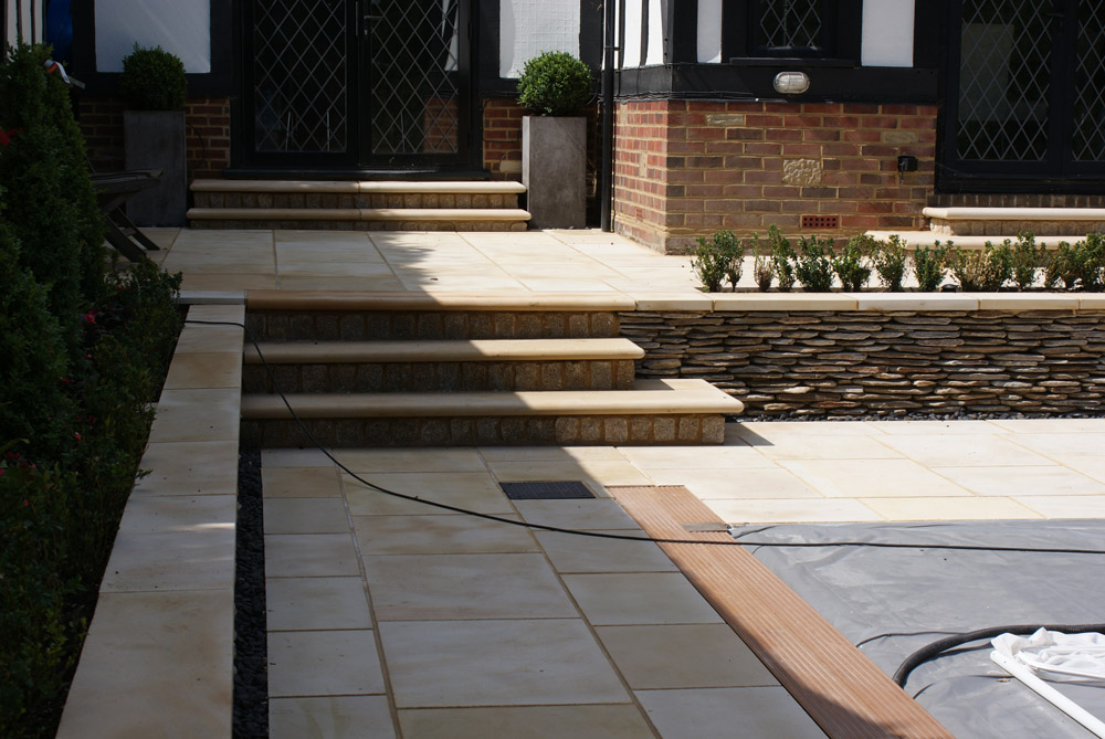 Buff sandstone steps and paving with yellow quartz paddlestones. Private garden designed by John Nash Associates and built by Robert Field Landscapes. For further images of this job please visit our Projects-Private Places gallery.