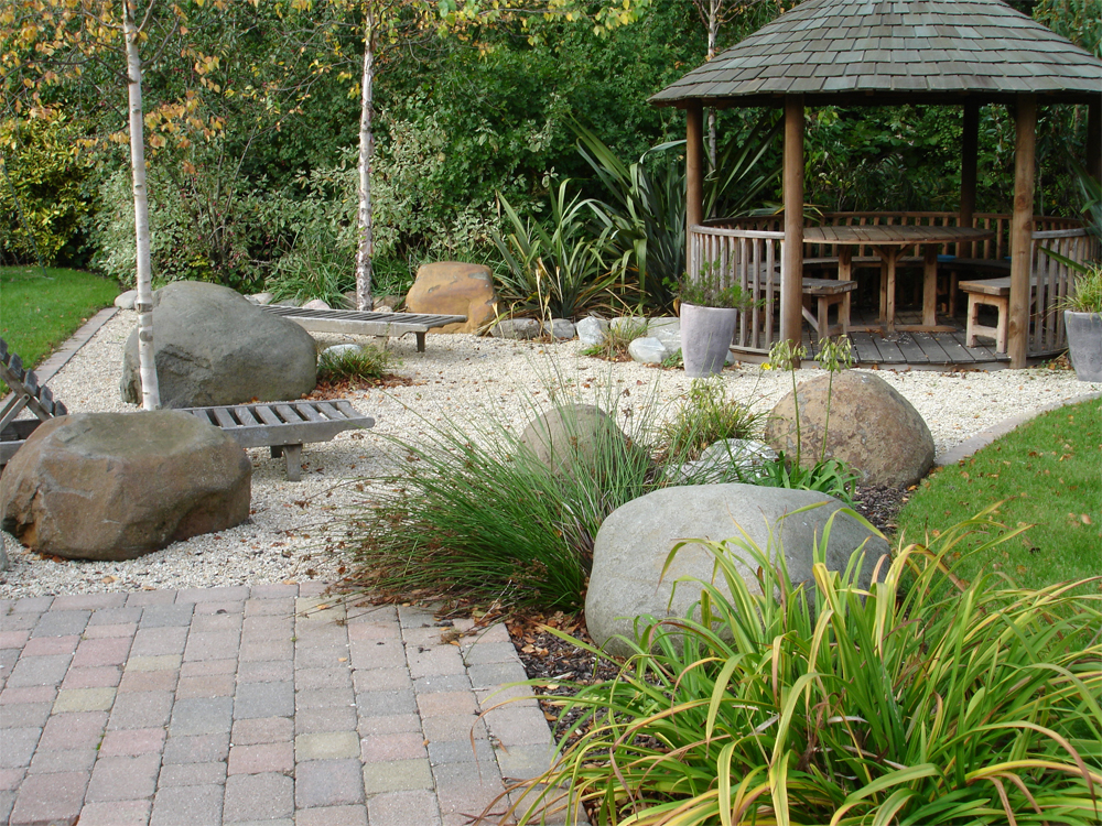 Buff Thames Aggregate with Caledonian Boulders. Private Garden' designed and built by New Eden Landscapes.