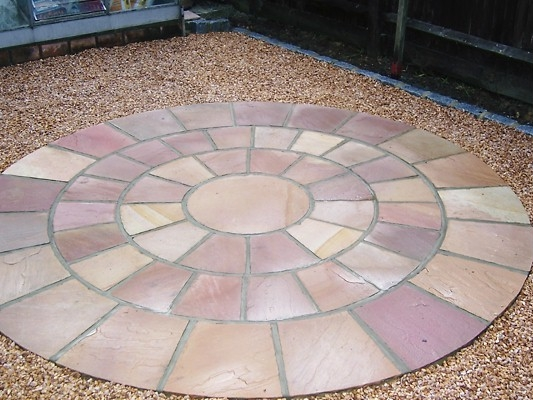 Golden flint gravel with a pink sandstone circle' private garden.