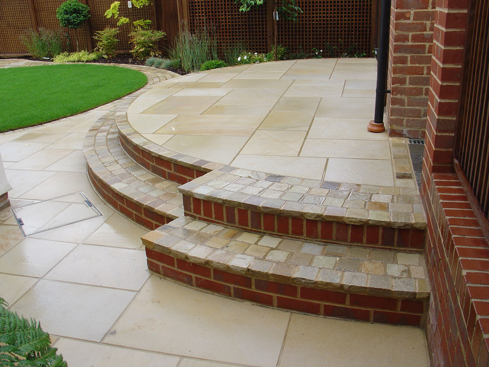 Green riven sandstone setts 100x100mm with buff green sandstone paving. Private garden designed and built by Oakview Landscapes.