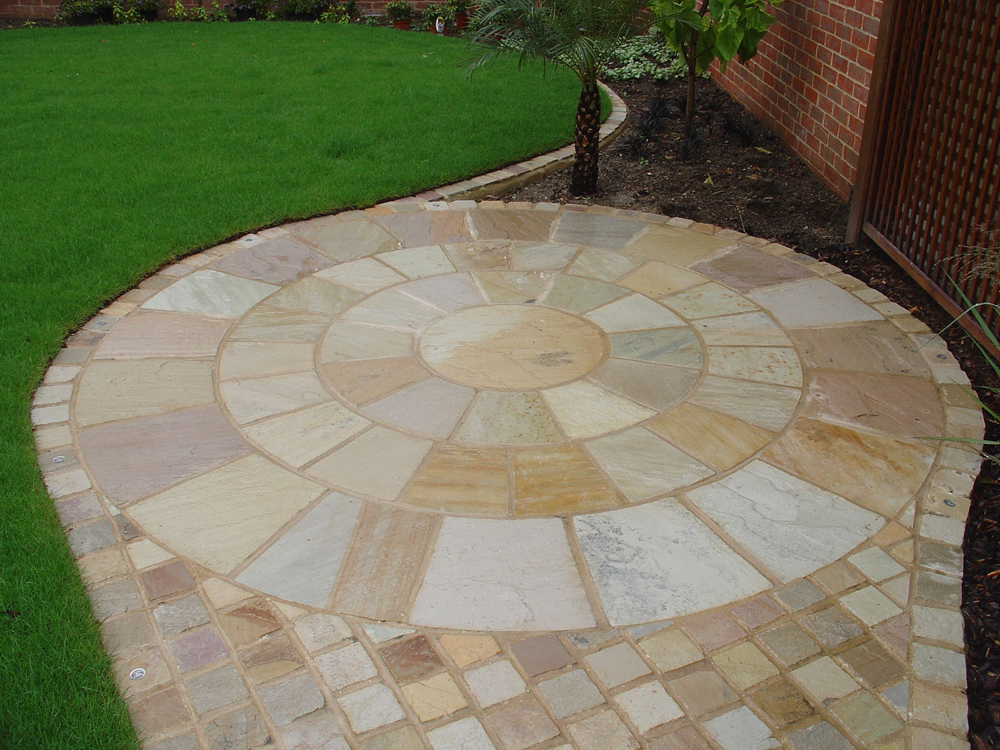 Green riven sandstone setts 100x100mm with a green riven sandstone circle. Private garden designed and built by Oakview Landscapes