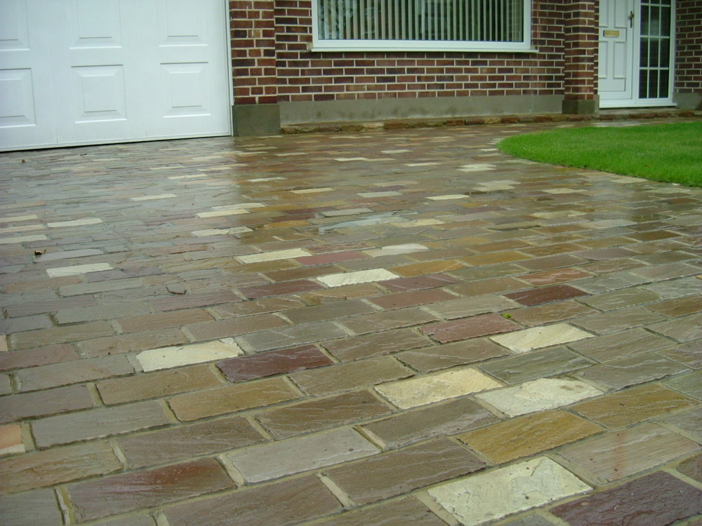 Riven Sandstone Setts 100x200x40-70mm (pictured here when wet). 80% Beige' 10% Green and 10% Pink. Designed and built by John Charles Landscapes.