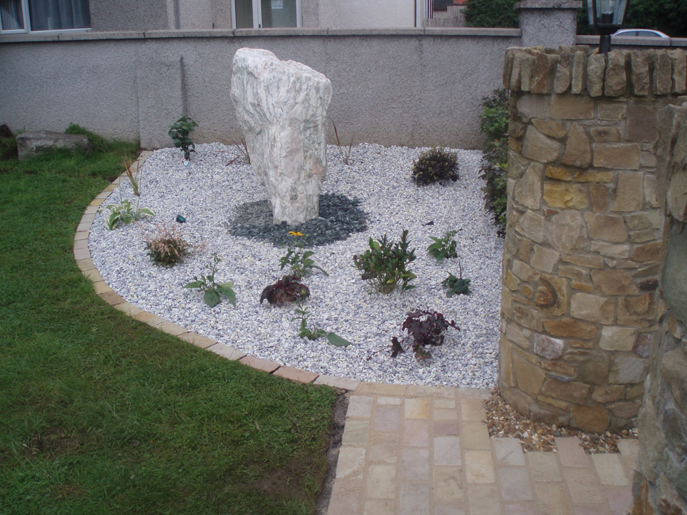 Green riven sandstone setts with a Norwegian rose feature stone' meadowgrass marble aggregate and green slate shale. Private garden' in Ireland' designed and built by Maurice Maxwell Garden Designs.