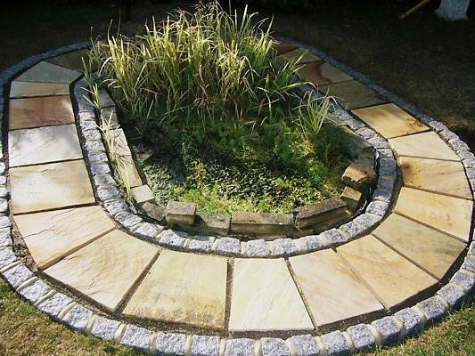 Green Riven Sandstone Paving' with silver grey granite cropped setts. Garden feature in private residence.