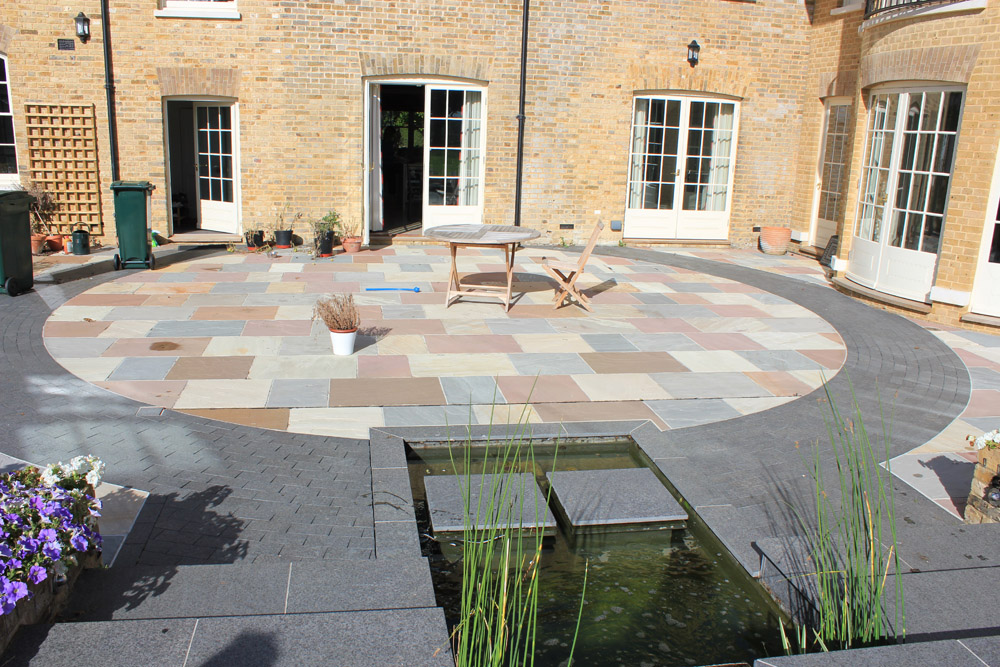 A mix of green' grey and pink riven sandstone paving with black basalt paving and imperial setts. Private garden designed and built by Baylis Landscapes. For further images of this job please visit our Projects-Private Places Gallery.