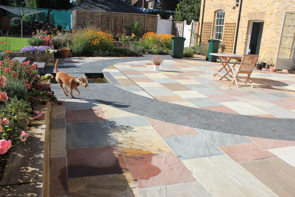 A mix of green' grey and pink riven sandstone paving with black basalt imperial setts. Private garden designed and built by Baylis Landscapes. For further images of this job please visit our Projects-Private Places Gallery.