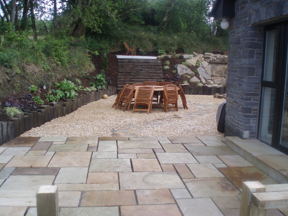 Green riven sandstone paving with buff flint gravel 20mm and buff sandstone rockery. Private garden in Ireland designed and built by Maurice Maxwell Garden Designs.