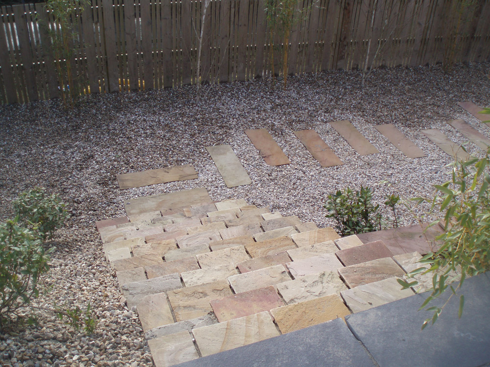 Green riven sandstone with buff flint gravel 10mm' golden flint gravel and black limestone. Private garden in Ireland designed and built by Maurice Maxwell Garden Designs.