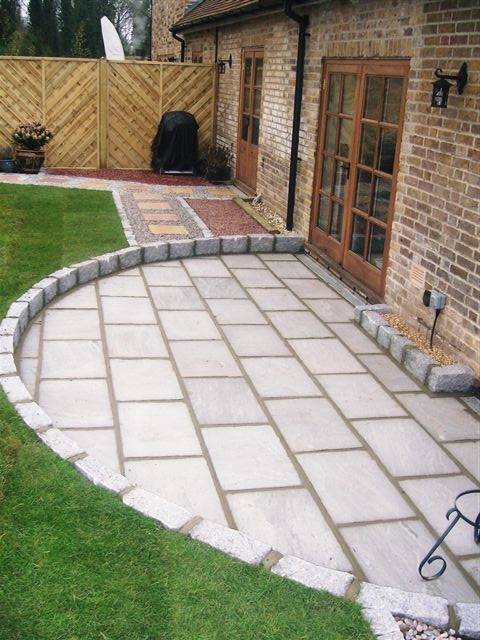 Grey riven sandstone paving with dark grey cropped granite setts. Designed and built by John Charles Landscapes.