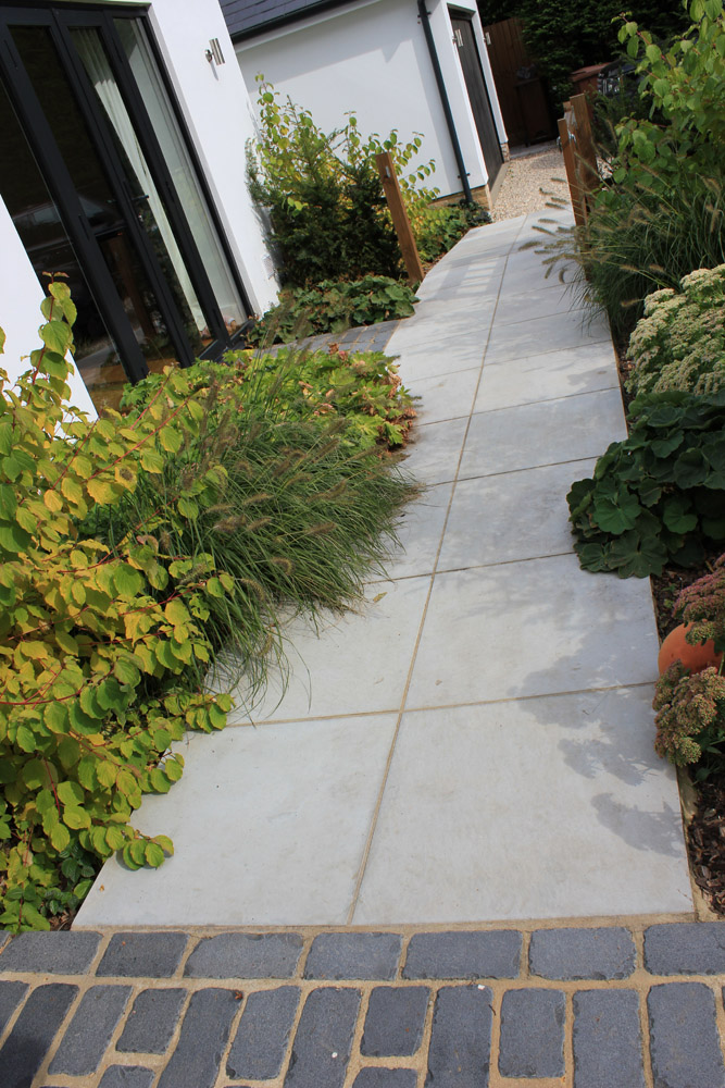 Grey sawn and sandblasted sandstone paving and black basalt temple setts. Private garden designed and built by New Eden Landscapes. For further images of this job please visit our Projects-Private Places Gallery.