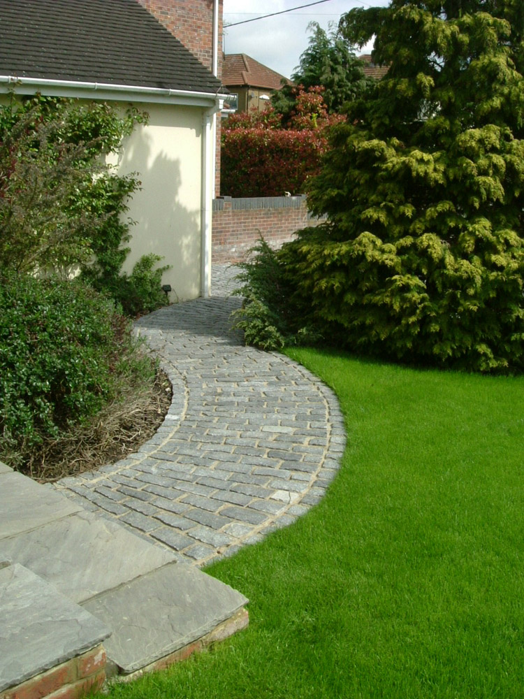 Grey riven sandstone paving (pictured here when wet) with dark grey cropped granite setts. Designed and built by John Charles Landscapes.