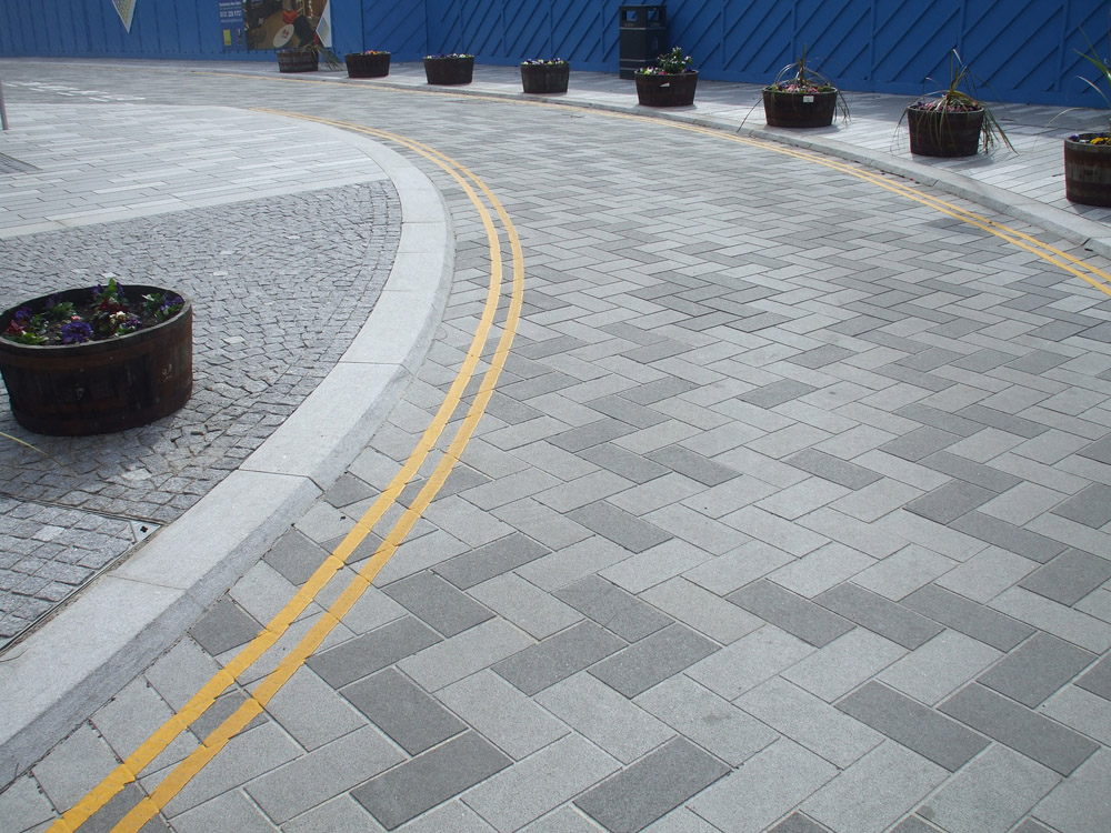 Silver grey granite kerb with granite and basalt setts and benches at Springside' Edingburgh. For further images and information on this project please visit our Projects-Public Spaces gallery.