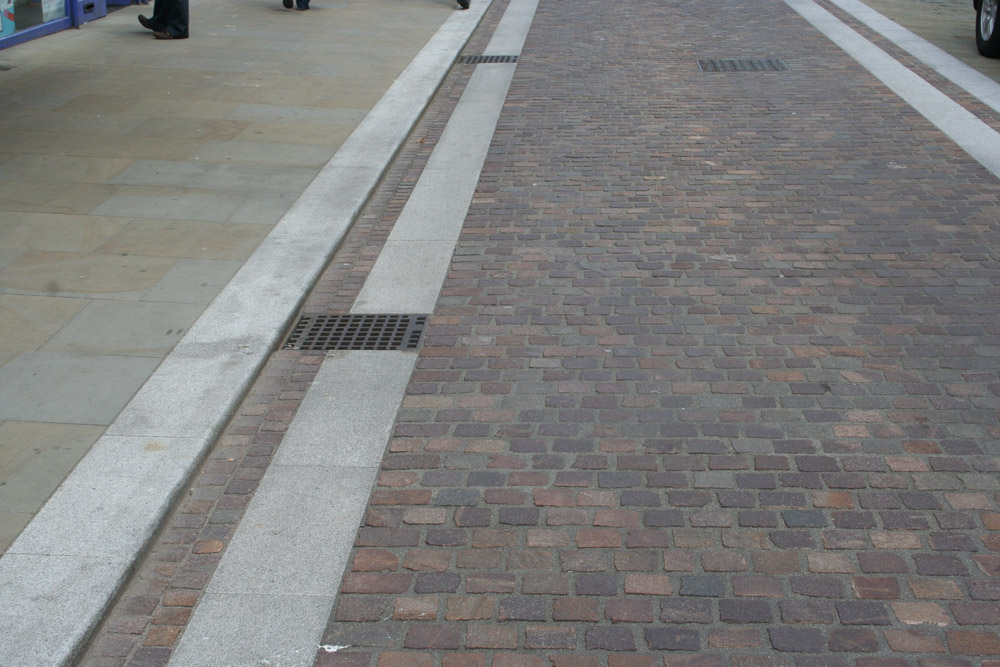 Silver grey granite kerb and paving with Porphyry setts in Widemarsh Street' Hereford. For further images and information on this project please visit our Projects-Public Spaces gallery.