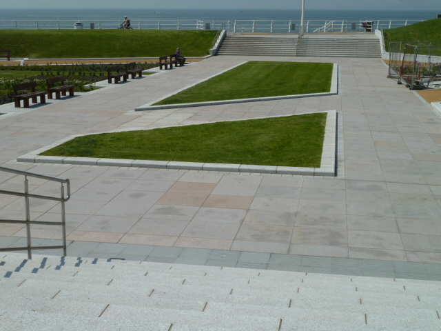 Pink granite paving with silver grey granite kerb' setts and steps at Aberafon Seafront' Wales. For further images and information on this project please visit our Projects-Public Spaces gallery.