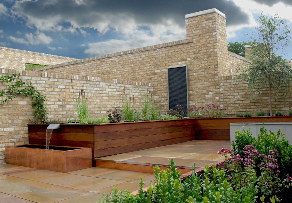 Pink sandstone paving' pictured here when wet' by Paul Dracott Garden Design.