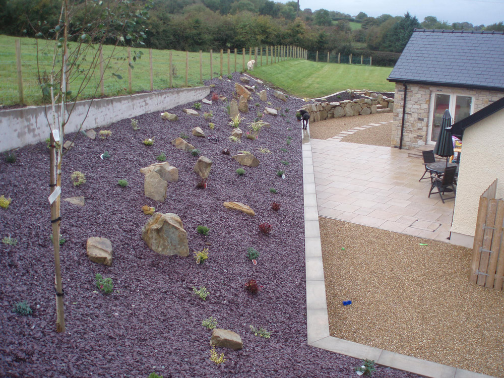 Plum slate shale (pictured here when wet) with yellow granite paving' golden flint gravel and buff sandstone rockery. Private garden' Ireland. For further images on this job please visit our projects gallery.