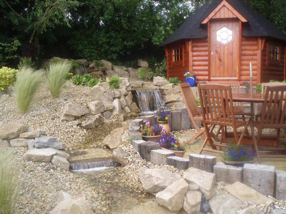 Buff quartz aggregate' buff sandstone rockery and reclaimed sleepers. Both the aggregate and rockery are local materials used for this private garden in Ireland.
