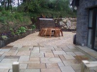 Buff sandstone rockery (local to this private garden in Ireland) with buff flint gravel 10mm and 20mm' green riven sandstone paving and circle and meadowgrass marble aggregate.