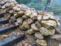 Golden quartzite rockery and Tabriz (silver grey / purple granite) paving at a private property.