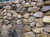 Golden quartzite rockery walls and Tabriz (silver grey / purple granite) paving at a private property.