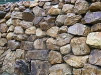 Golden quartzite rockery walls and Tabriz (silver grey / purple granite) paving at a private property.