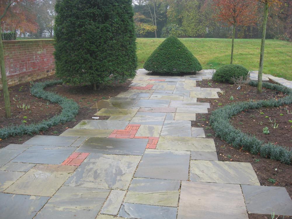 Riven yorkstone paving in a private garden. Designer - Julie Toll Ltd. Contractor - Brambledown Landscapes.