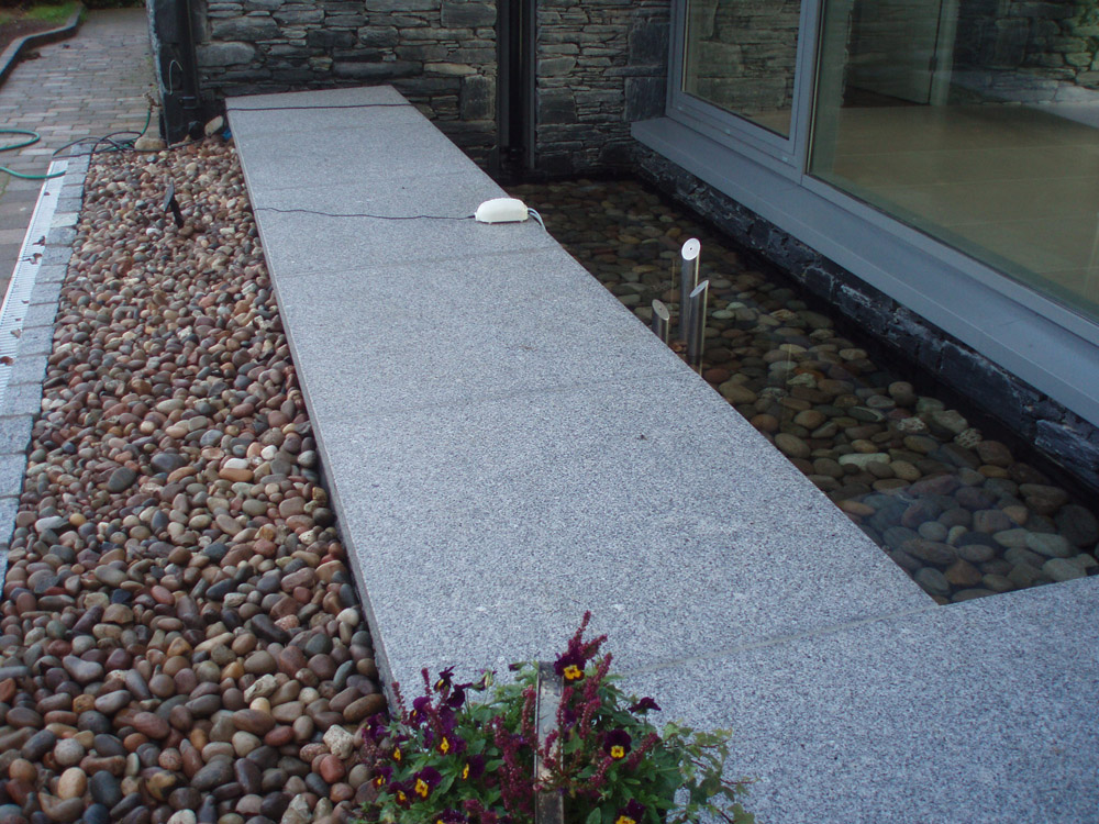 Silver grey granite paving (pictured here when wet) with Scottish beach pebbles and silver grey (8R) cropped setts. Private garden' in Ireland' designed and built by Ben McKee Landscapes.