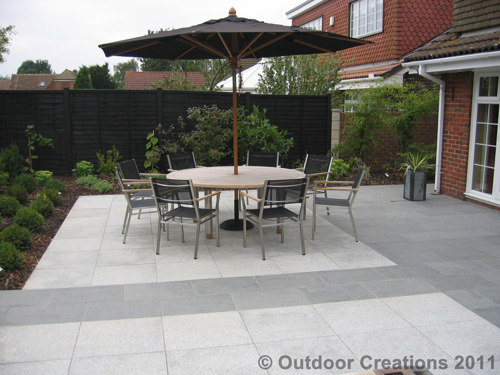 Silver grey granite paving with blue grey granite paving. Private patio designed and built by Outdoor Creations.