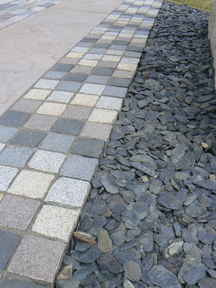 A mix of all 5 colours (black' blue/grey' pink' silver/grey and yellow) of split sided Imperial Setts' next to Rustic Slate Shale' at the BALI Landscape Show 2012.
