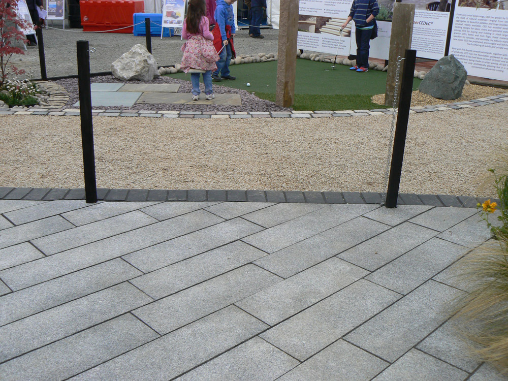 Silver Grey granite plank paving at the Balmoral Show. Also pictured are black riven limestone setts' Irish barley quartzite aggregate' temple setts' blue limestone and riven yorkstone paving' large Scottish beach cobbles and golden flint gravel aggregate. For further images and info of this garden please visit our Private Places-Show Gardens Gallery.