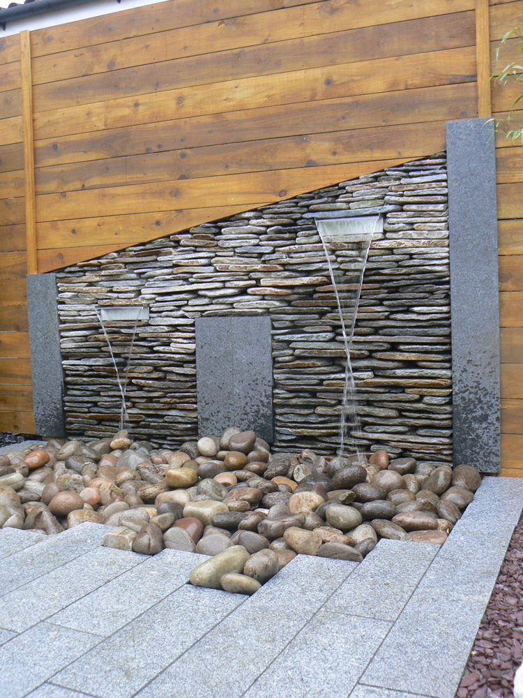 Silver grey granite plank paving leading to a water feature built up by black quartz paddlestones and Scottish beach cobbles at the Balmoral Show. For further images and info of this garden please visit our Private Places-Show Gardens Gallery.