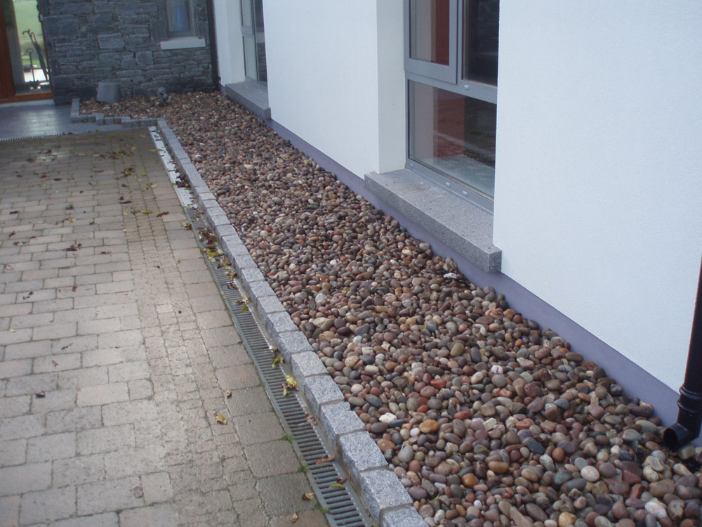 Silver grey (8R) cropped granite setts with Scottish beach cobbles (pictured here when wet. Private garden' in Ireland' designed and built by Ben McKee Landscapes.