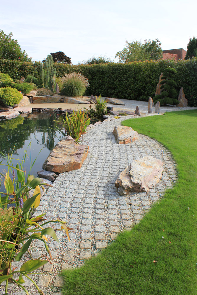 Silver grey granite (8R) cropped setts in a private garden. Also pictured is silver grey granite aggregate and purple standing stones. Garden designed and built by J. Wenman & Sons. For further images of this job please visit our Projects-Private Places Gallery.