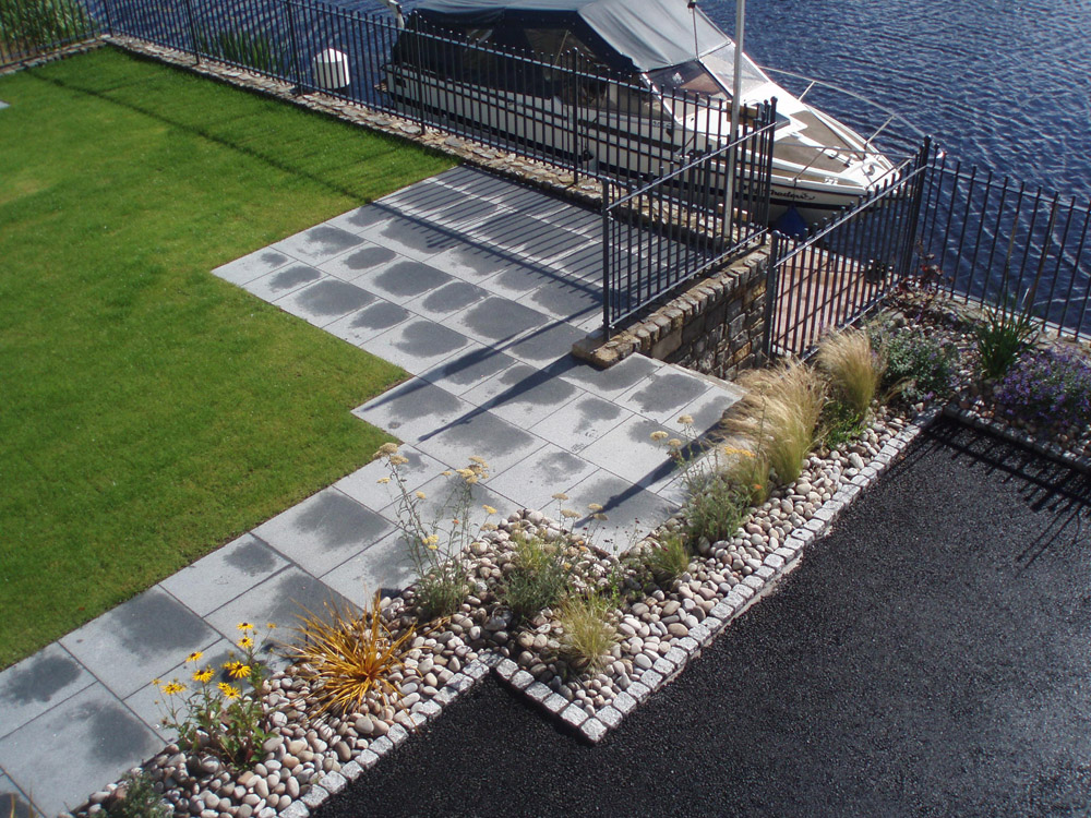 Silver grey (8R) cropped setts with Scottish beach cobbles and blue grey granite paving. Private garden' in Ireland' designed by Maurice Maxwell Garden Designs and built by Spring Landscapes. For further images of this job please visit our Projects Gallery.