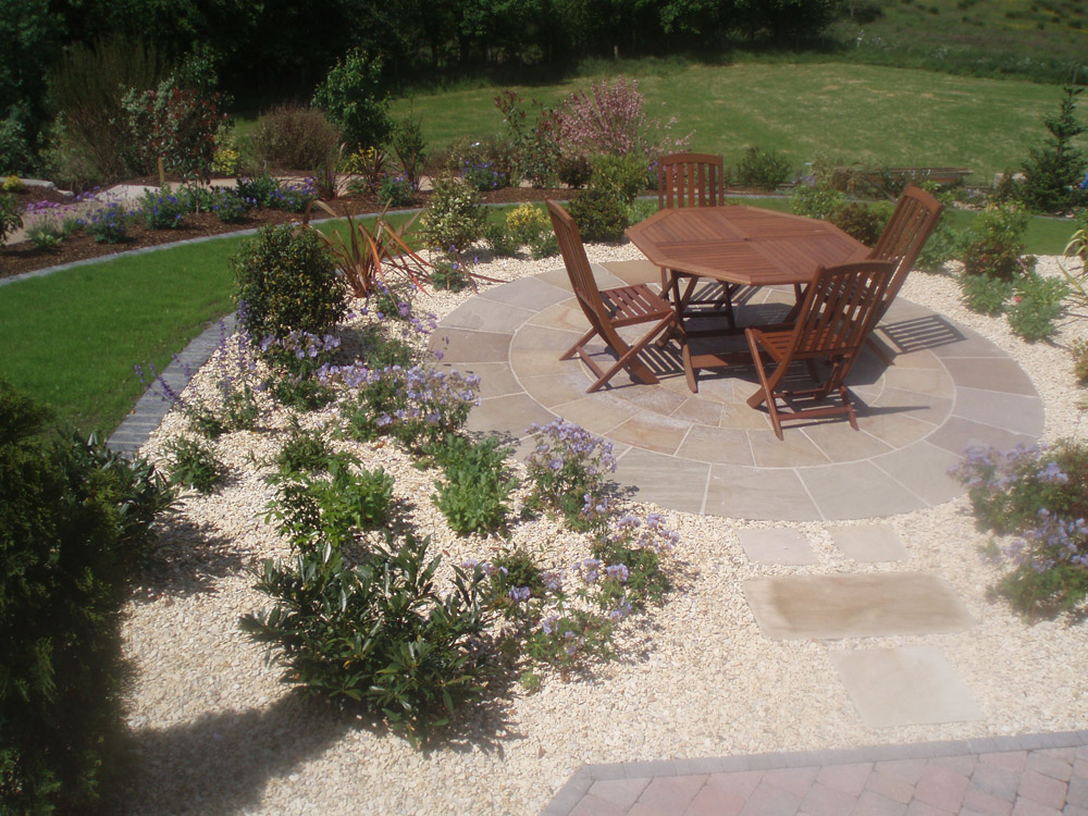 Beige sandstone circle and paving with buff flint gravel. Private garden in Ireland designed and built by Maurice Maxwell Garden Designs.